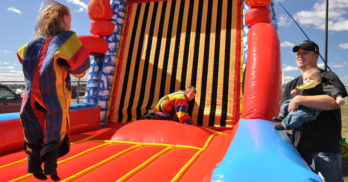 kids jumping on an inflatable velcro wall
