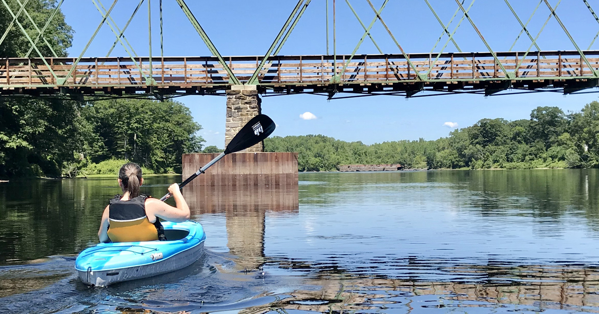 a girl on a kayak about to go under a bridge