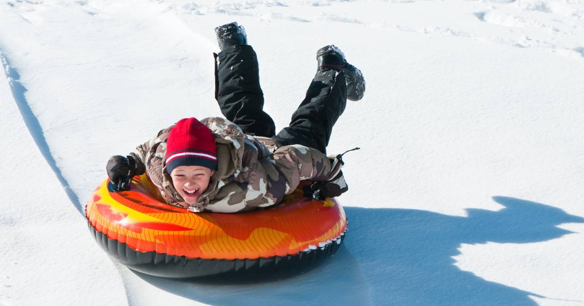 kid snow tubing down a hill