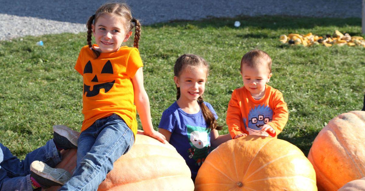 kids sitting on pumpkins