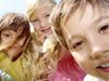 close up of three kids looking at camera