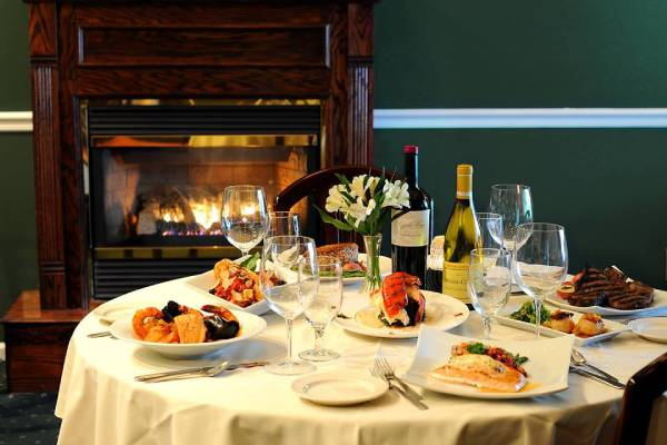 dinner table with wine and plates of food near a fireplace