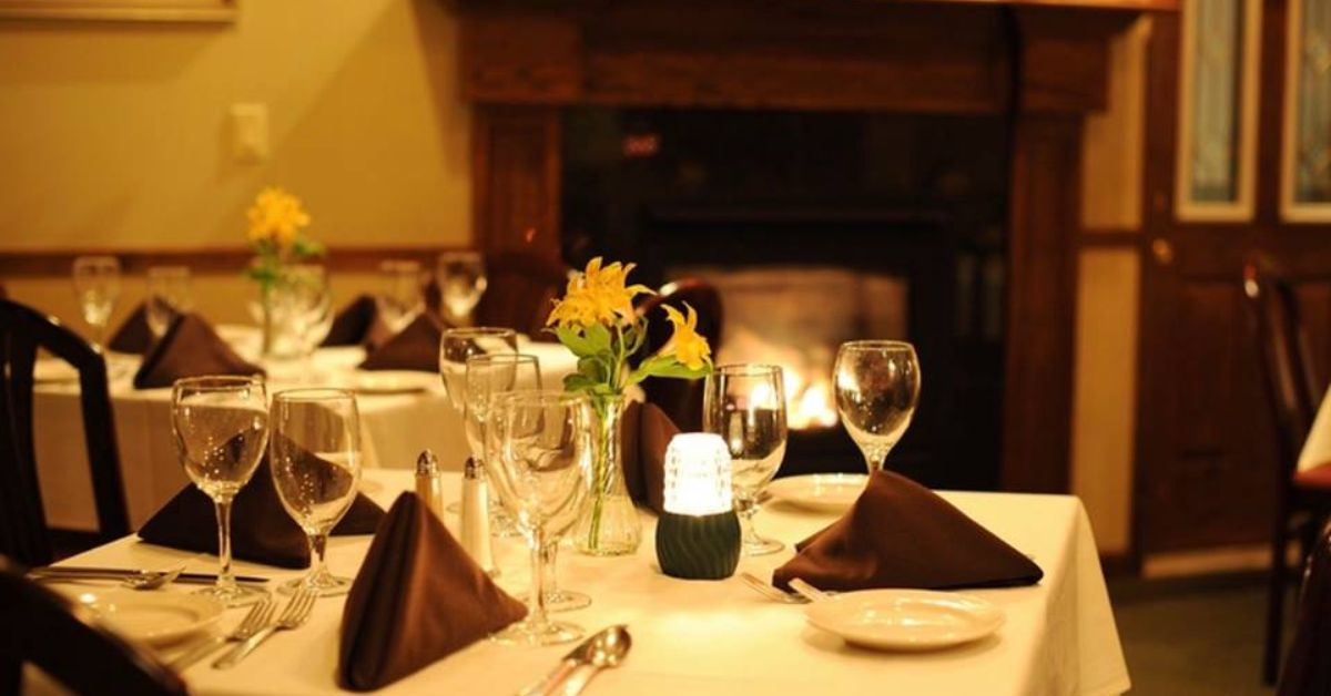 restaurant dinner table with fireplace at the back of the room