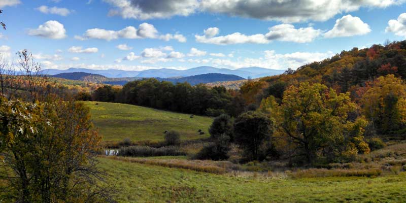 scenic view of fields, trees, mountains, and clouds