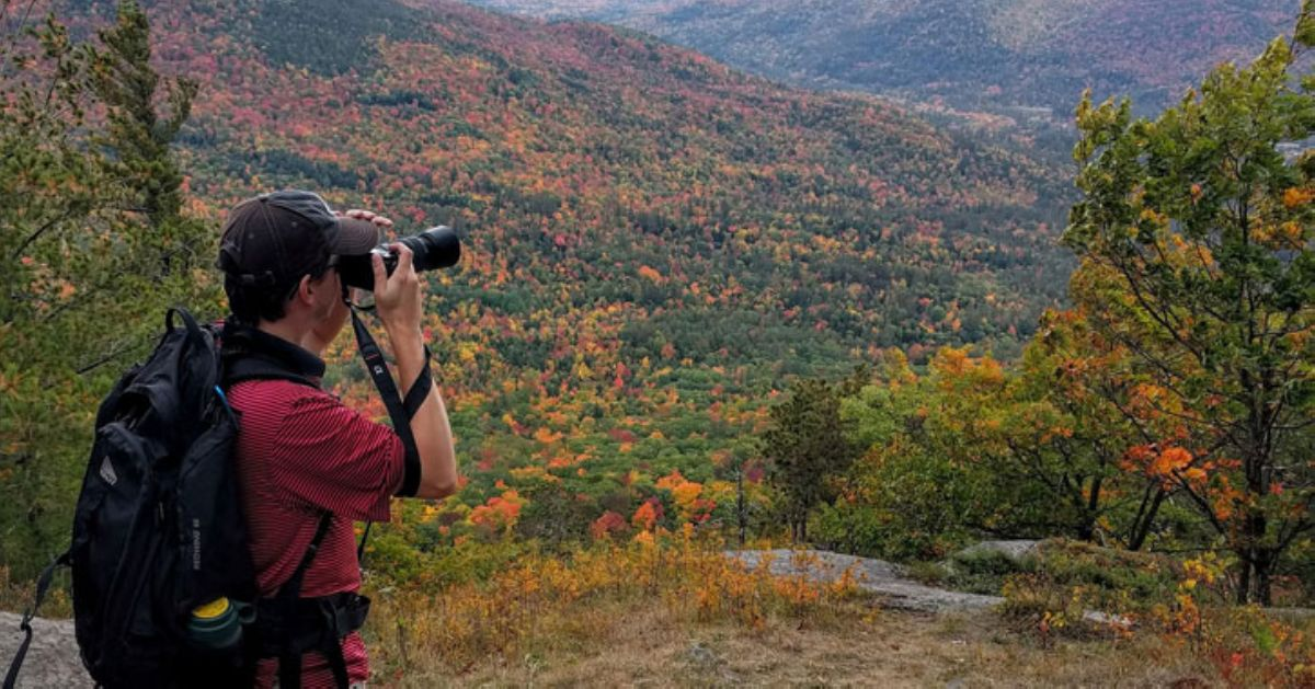 man with camera photographing mountains with fall foliage