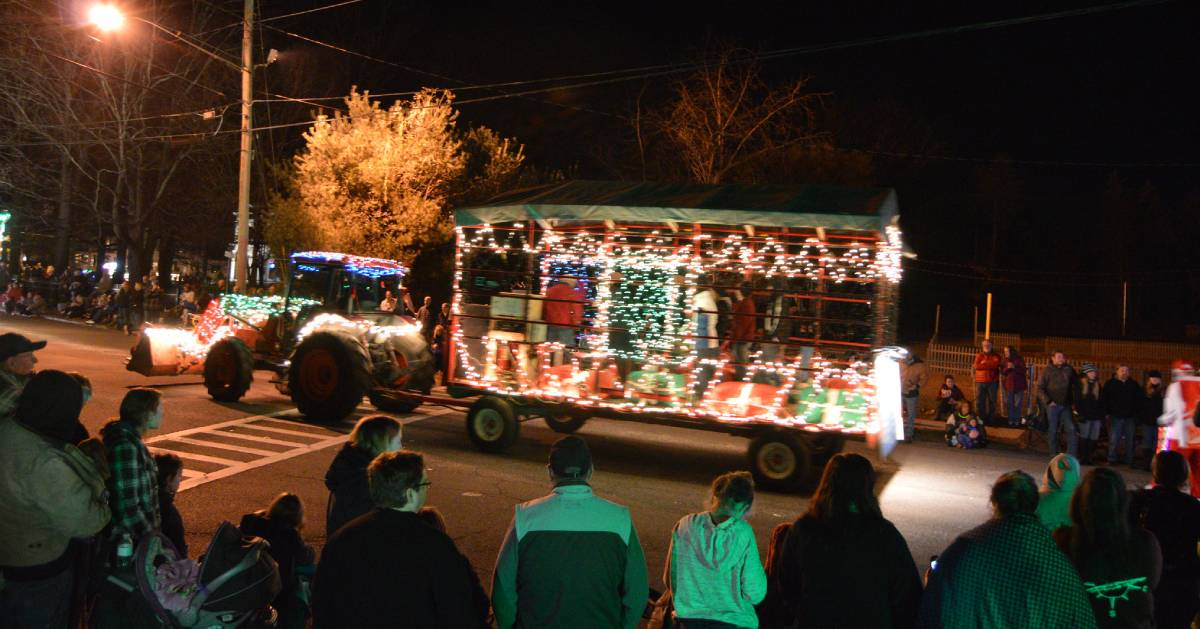 lighted tractor parade with people watching