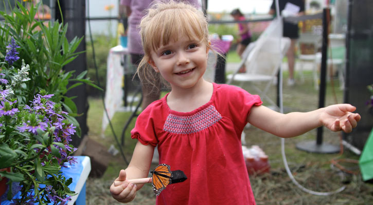 little girl in red holding a stick with a monarch butterfly on it with one hand while holding out her other hand, grinning