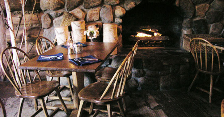 tables set up by a stone fireplace