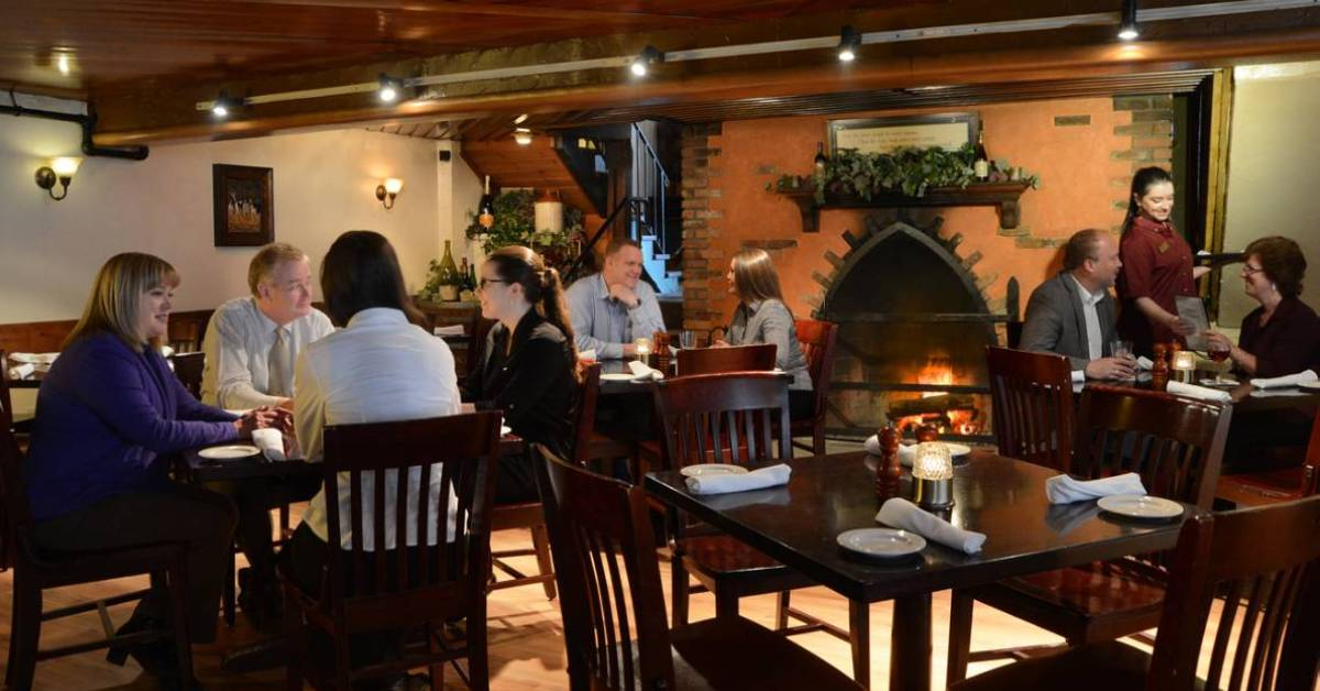 people in a dining room with a big fireplace