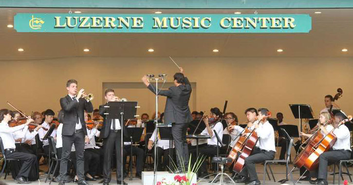 a conductor conducting an orchestra, sign above them saying Luzerne Music Center