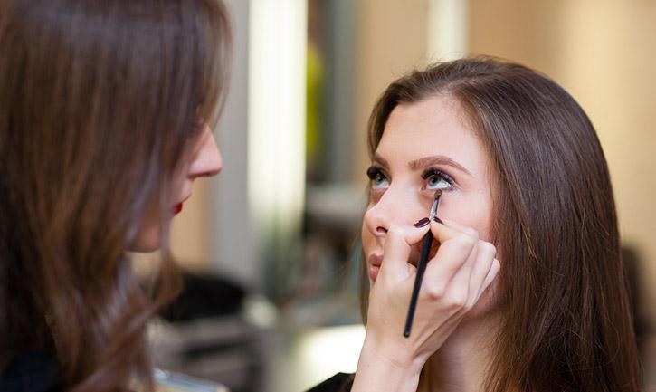 woman getting eyeshadow put on