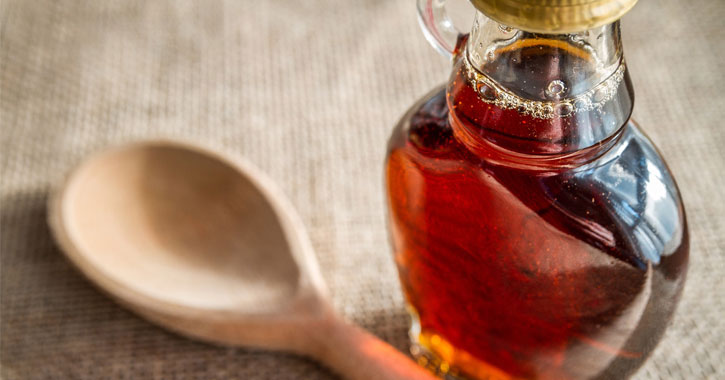 da21e978b11 a bottle of maple syrup next to a wooden spoon
