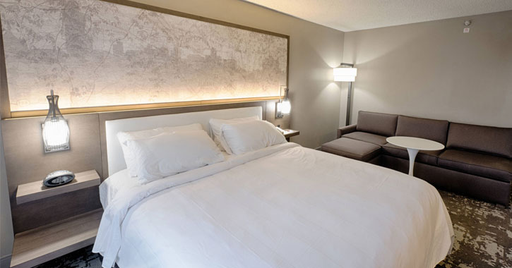 a white sheeted bed in a hotel room with a silhouette of the Albany skyline above it