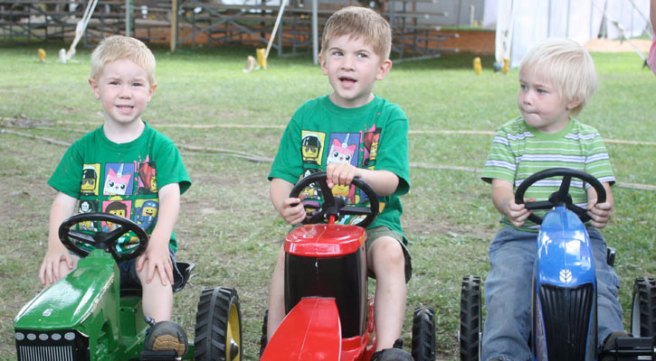 three little boys on mini tractors, the first two are wearing a matching green shirt, the third is wearing a nonmatching green shirt