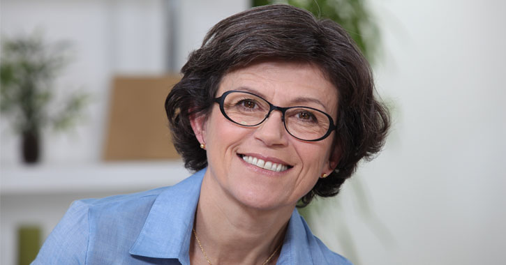 a smiling middle aged woman with dark hair and glasses