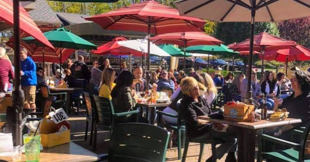 people dining on a patio with umbrellas