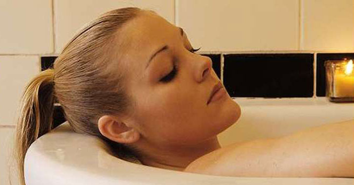 woman soaking in a tub with a candle