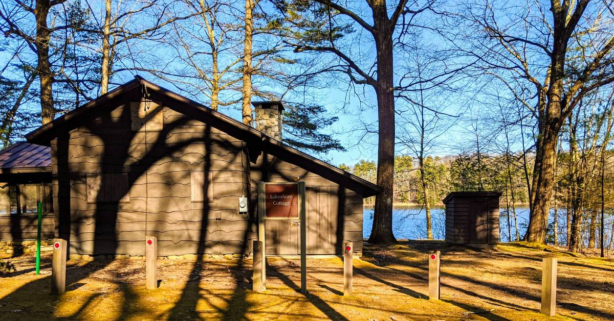 a cabin by trees and water