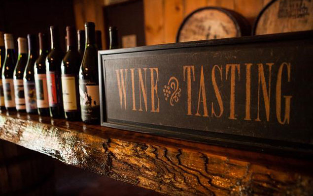 wine bottles and wine tasting sign
