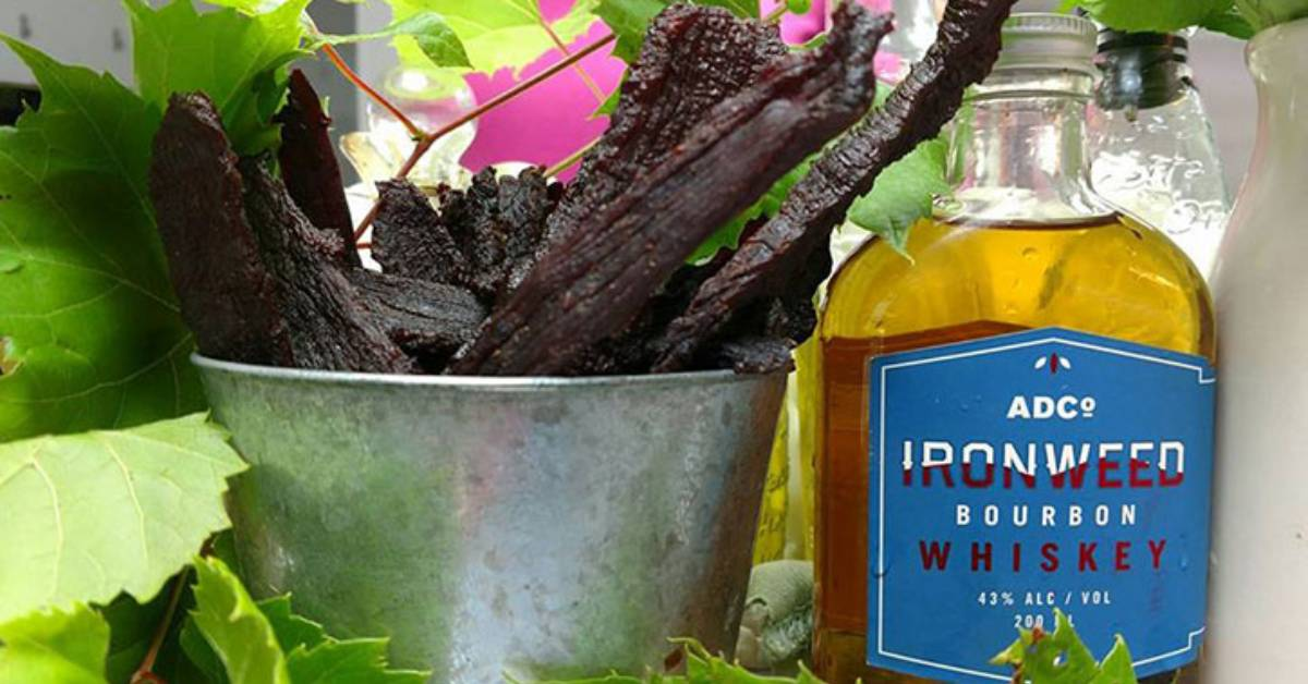 beef jerky on display in bucket next to whiskey