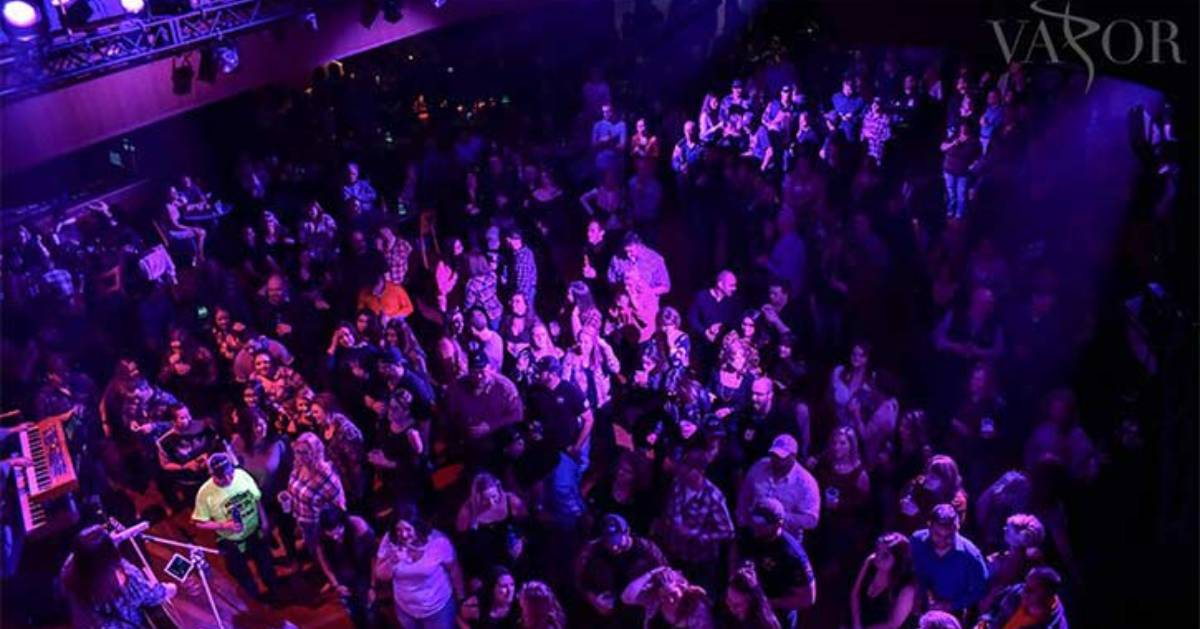 large crowd of people in a nightclub with purple lights shining