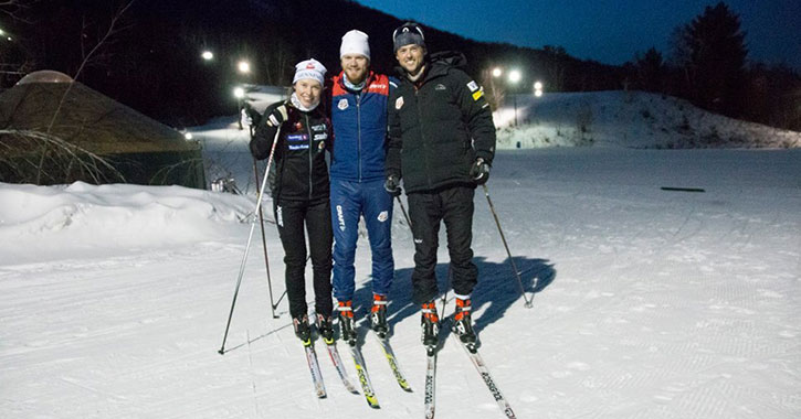 three skiers outside at night