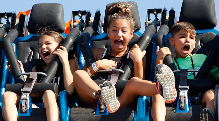 three kids on a ride screaming