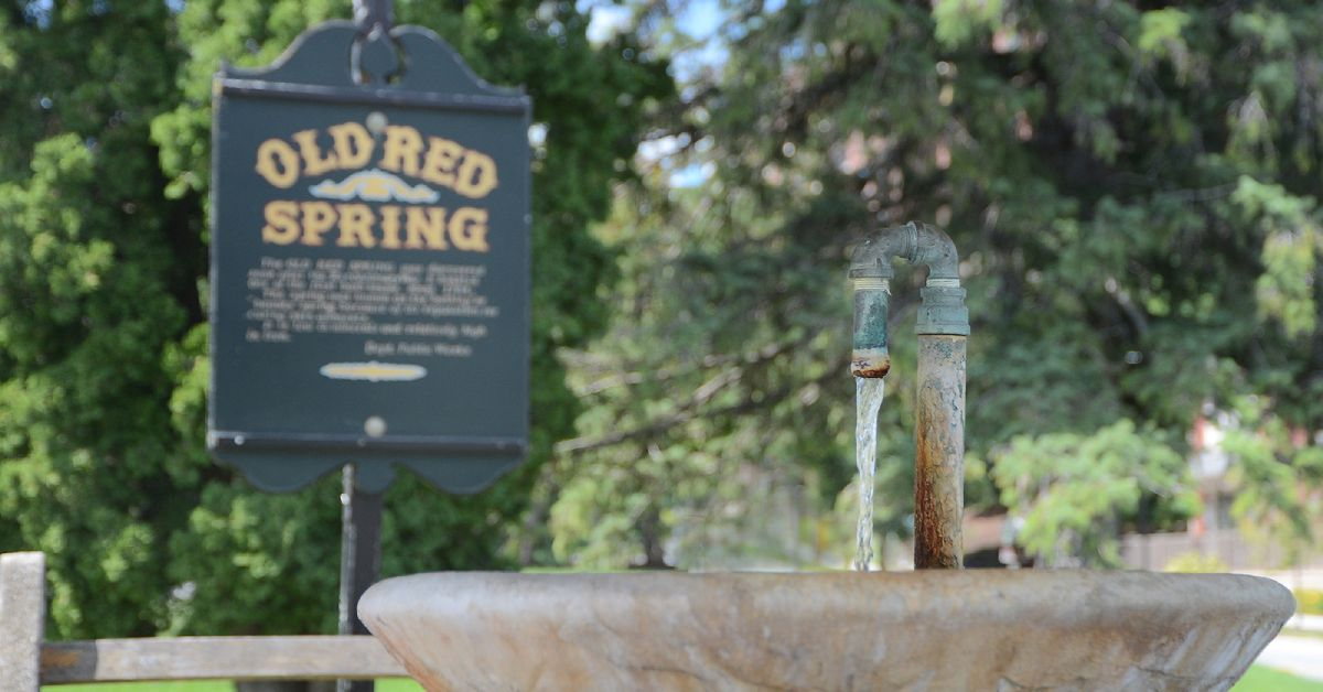 water coming out of old red spring, with its sign in the background