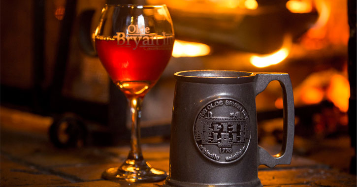 a glass and mug that say Olde Bryan Inn in front of a roaring fire