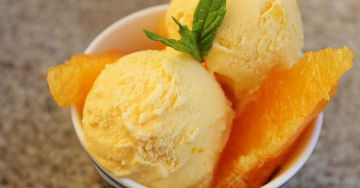 a bowl of two scoops of orange creamsicle flavoreed ice cream with oranges and a garnish