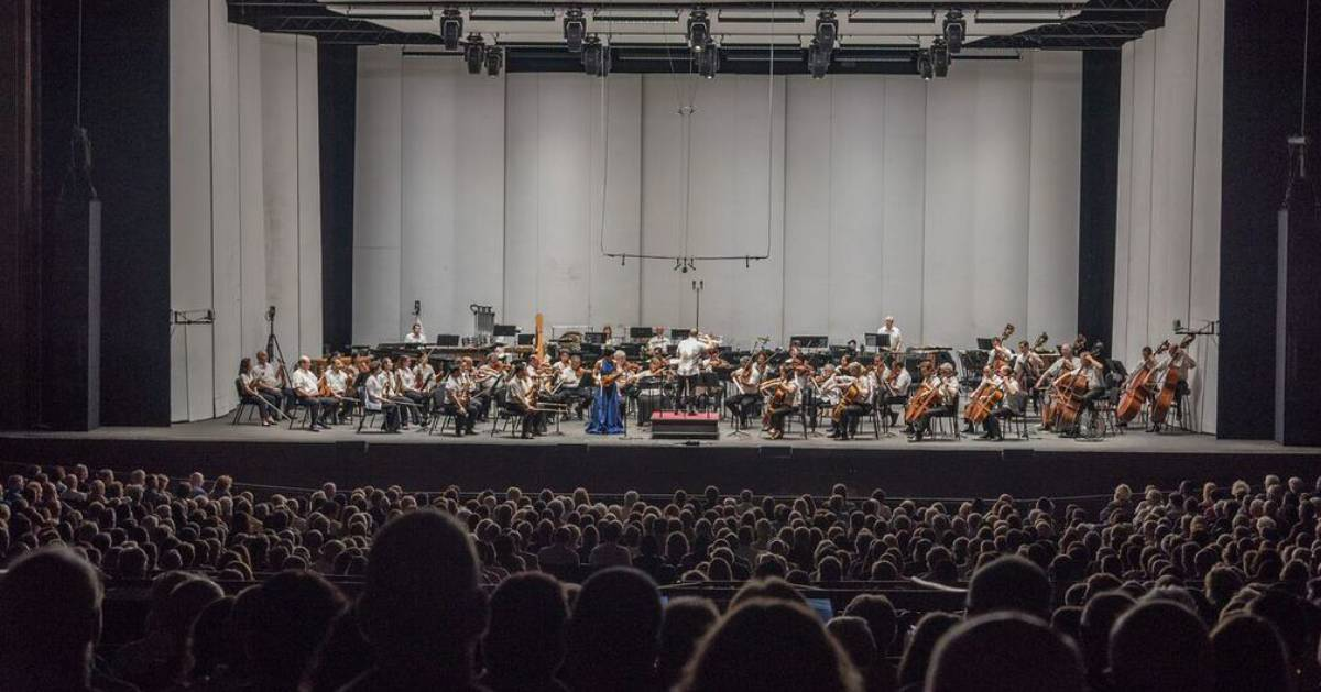 orchestra on stage and crowd watching