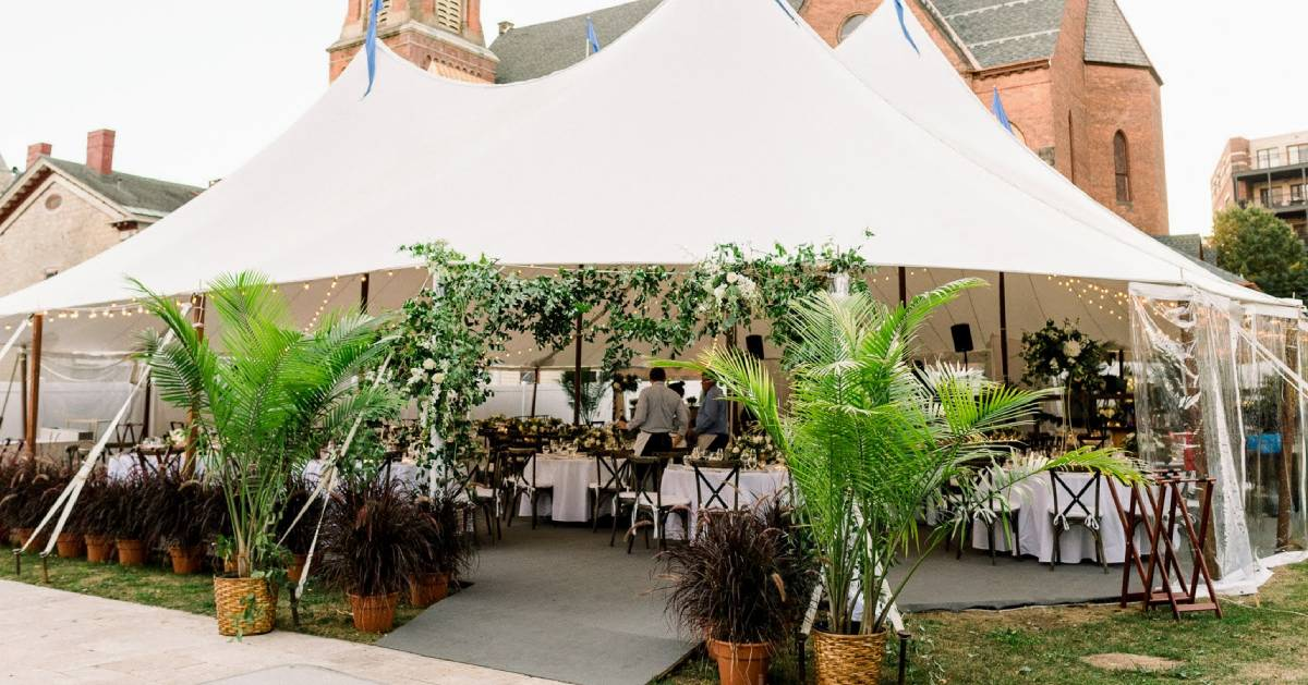 large outdoor tent set up with tables and chairs, plants