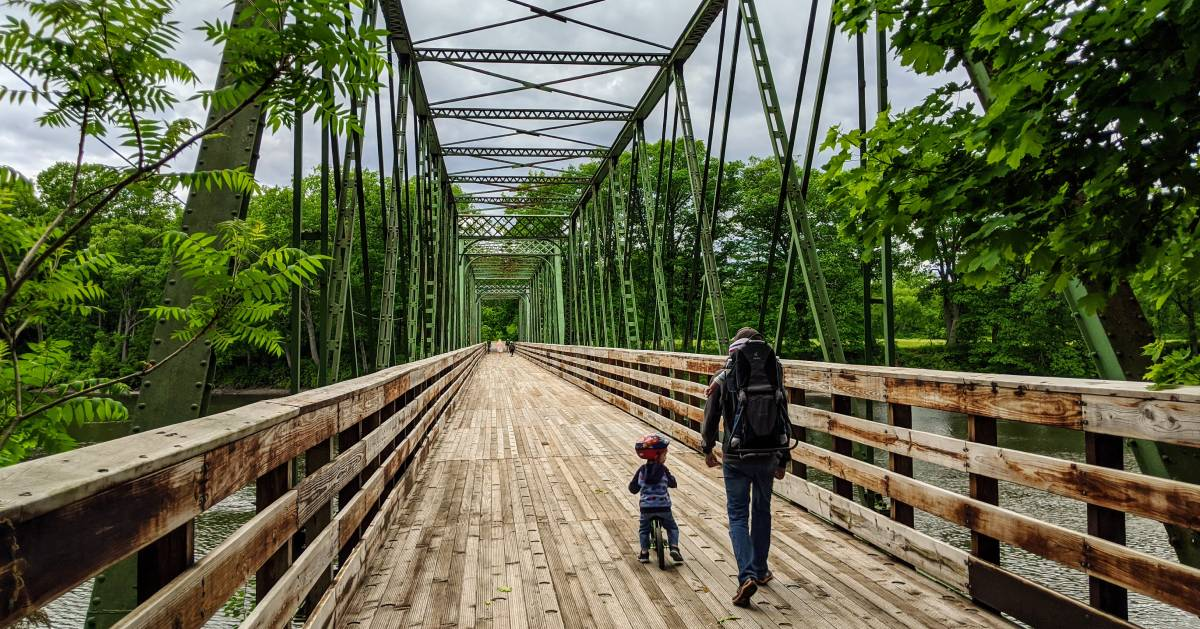 man and kid going over a bridge