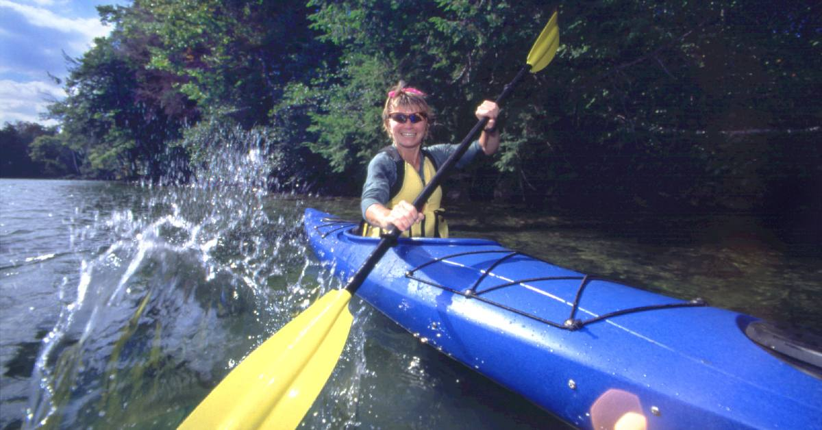 woman kayaking down a creek