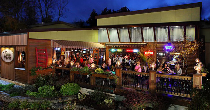 the outside of Peddler's Bistro at night, people on the deck