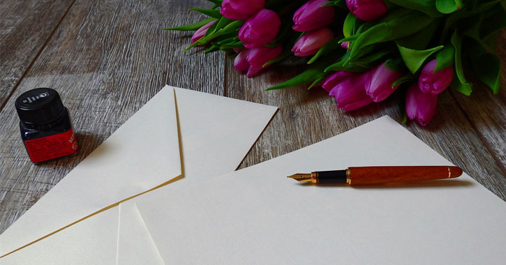 a fountain pen and paper and envelope with purple-like tulips