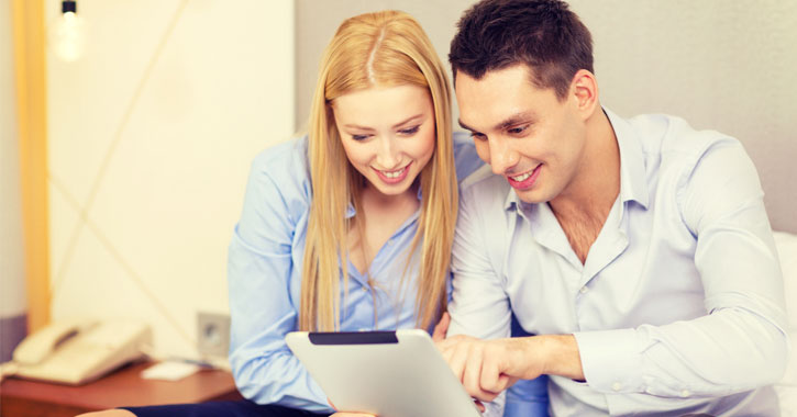 a couple smiling and looking at a tablet together