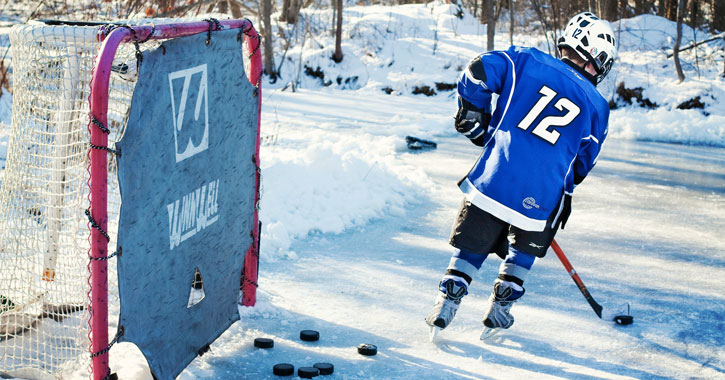 a young boy playing pond ice hockey with a goal nearby
