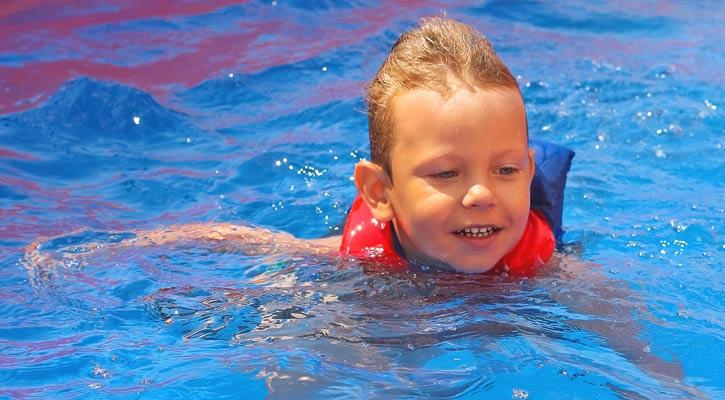 kid with life vest having fun in pool