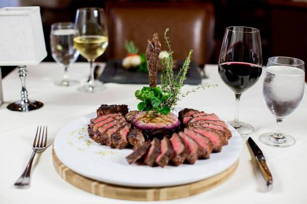 steak dinner on plate in restaurant with wine glasses nearby