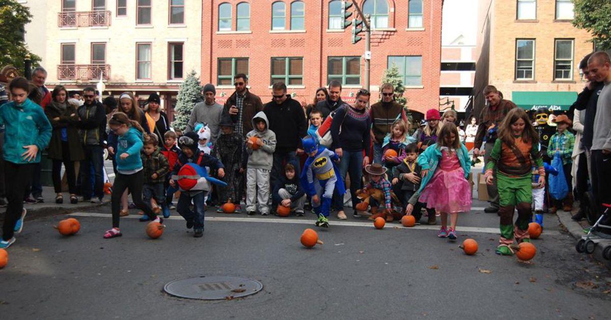 kids rolling pumpkins down road