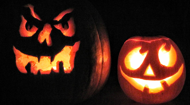 two jack-o-lanterns, one large and angry, one smaller and happy, next to each other, lit up in the dark