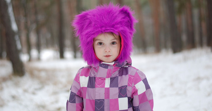 a little girl looking at the camera dressed in a purple and white coat and a purple fuzzy animal hat