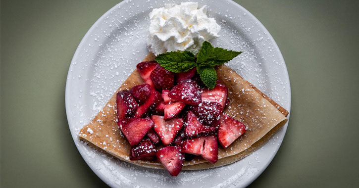 a crepe with strawberries and whipped cream
