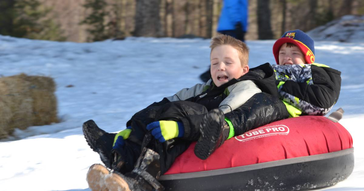 kids riding on a red snow tube