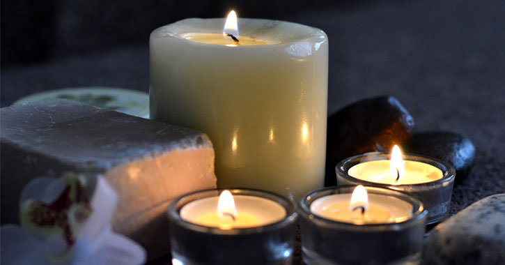 one large lit candle and three smaller lit candles with stones