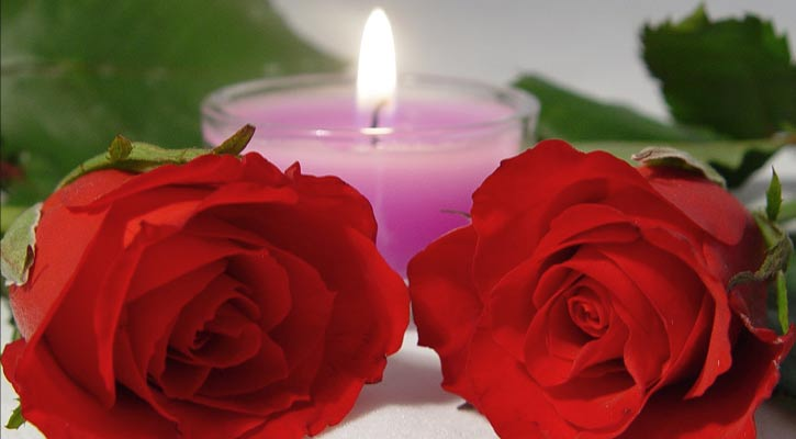 two red roses in front of a small, pink, lit candle