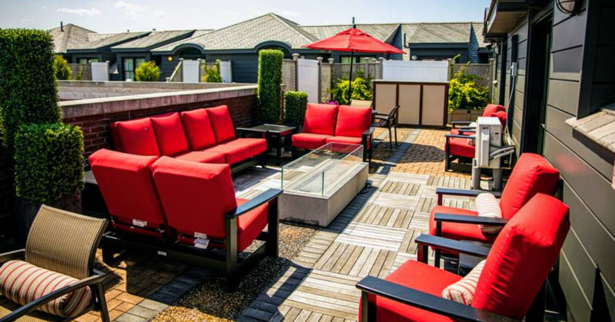 rooftop deck with red couches and chairs