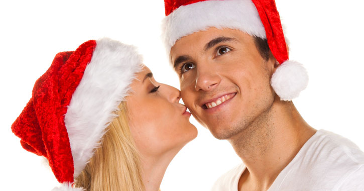 a couple in Santa hats, woman is kissing man on the cheek