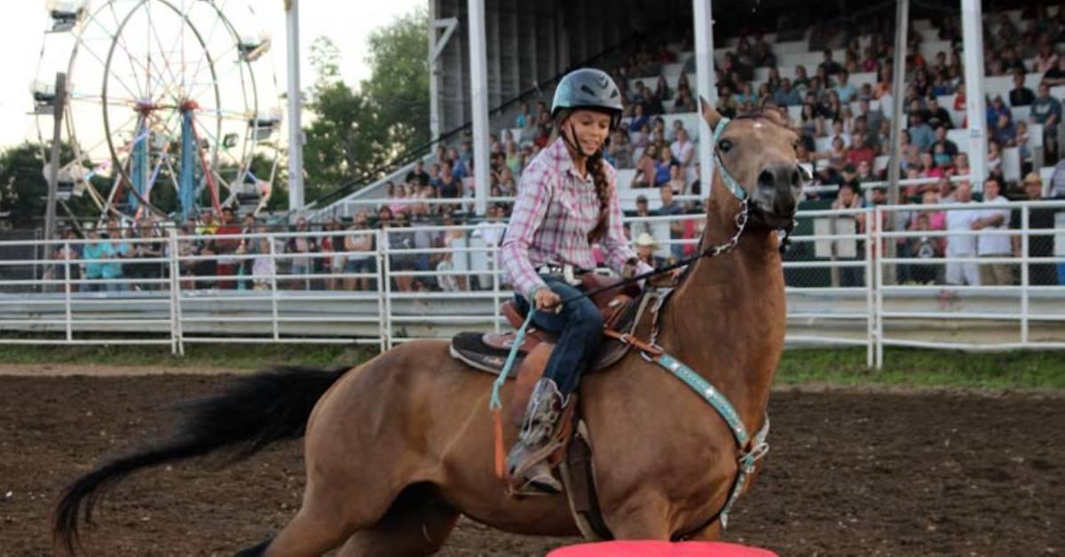 teenage girl riding a horse at a fair show